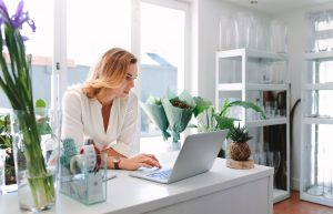 Female florist using laptop in flower shop